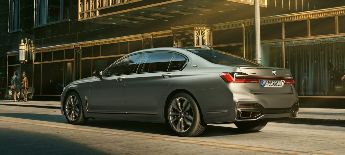 BMW M760Li xDrive Limousine, seitliche Heckansicht vor Wolkenkratzern in urbaner Kulisse
