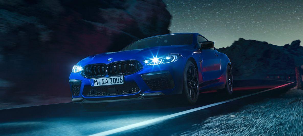BMW M8 Competition Coupé in Marina Bay Blau metallic mit strahlenden LED-Scheinwerfern, Dreiviertel-Frontansicht, fahrend bei Nacht.