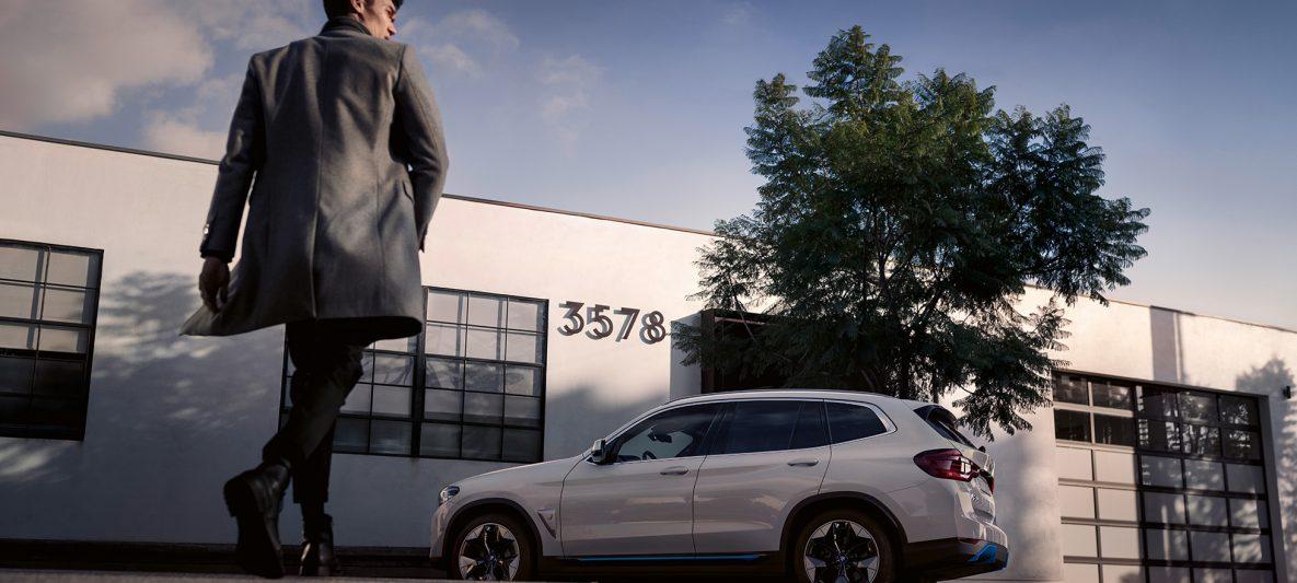 BMW iX3 G08 2020 Mineralweiß metallic Seitenansicht vor Gebäude mit Mann